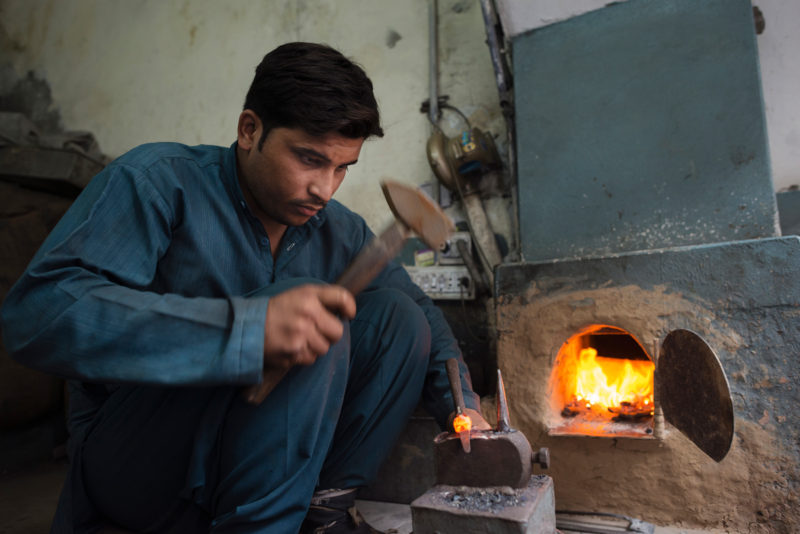 man using a hammer by oven