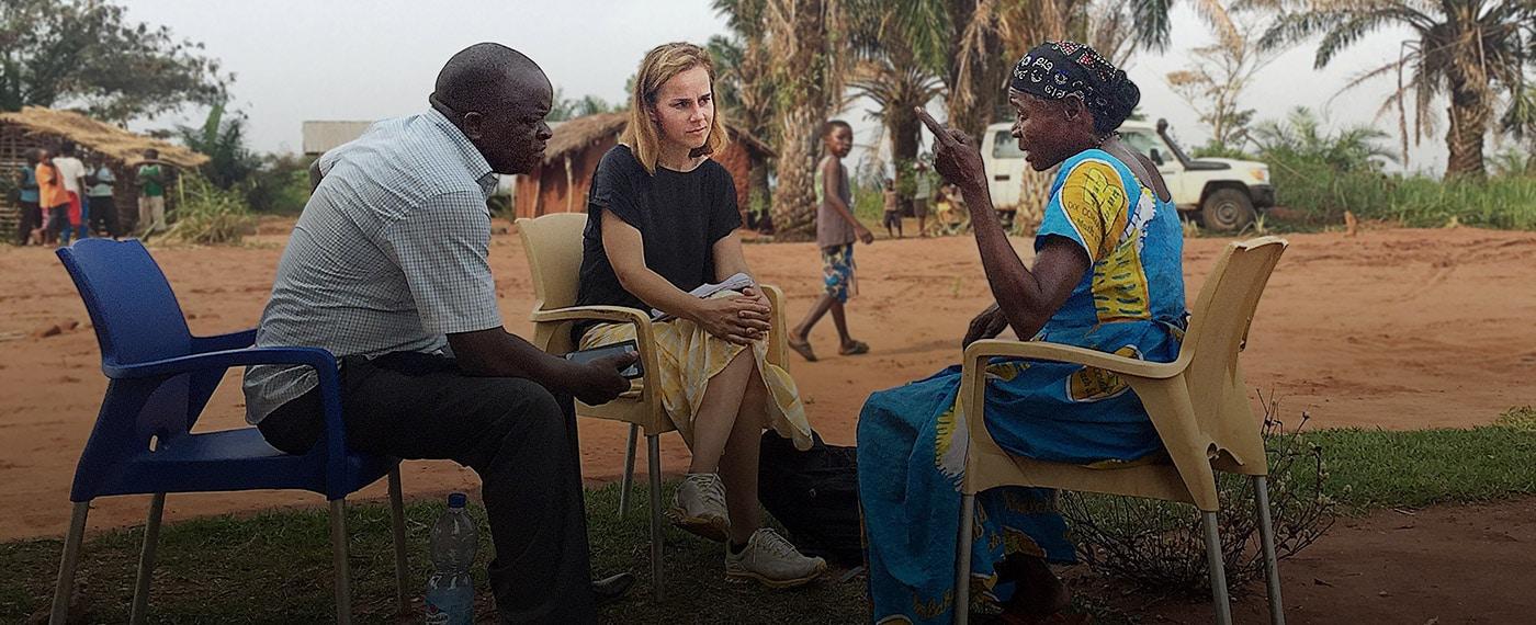 Vit kvinna som pratar med en svart man och en kvinna