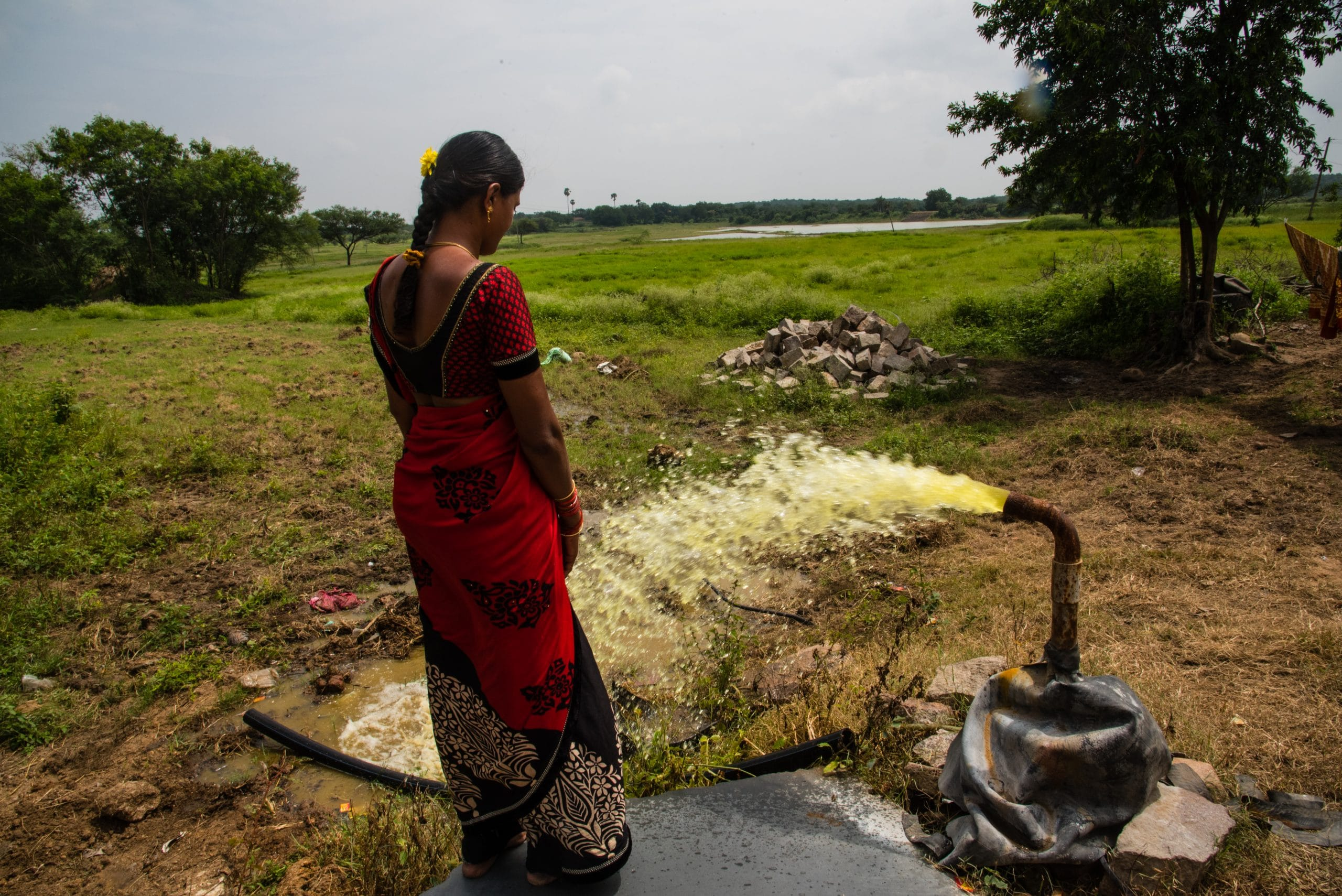 woman standing next to pipe that's spreading contaminated water